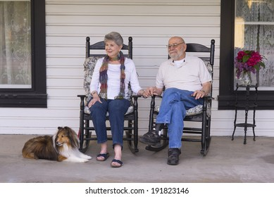 An elderly married couple in their eighties watch the world go by from their porch with their sheltie dog by their side.
