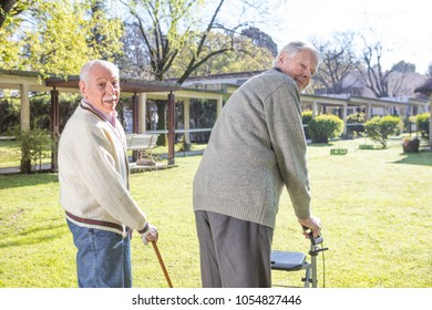 Elderly men with crutches outdoor happy with life.