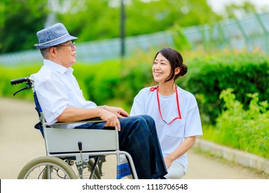 Elderly men riding in wheelchairs and caregivers