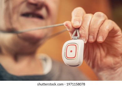 elderly and mentally disabled woman holds her home emergency call in her hand. button to call for help in case of emergency. home care service - emergency call for the elderly.