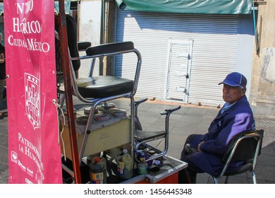 Elderly mexican man working as street shoe polisher (bootblack) sits near high shoeshine's chair and waits for next client.This work is his daily life, profession and income.Jan 2015,Mexico,Mexico