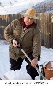 An elderly Minnesota man shovels snow in his backyard after a heavy snowfall.