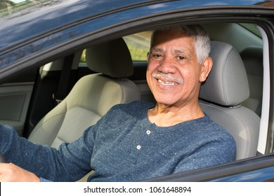 Elderly minority man driving in his new car