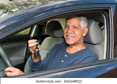Elderly minority man driving in his new car