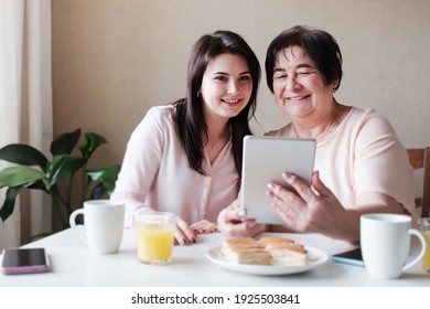 An elderly mother and an adult daughter are having fun at home using a tablet to view content on the Internet - Real family relationships of different generations and modern technologies in everyday