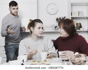 Elderly mother comforting her daughter after discord with husband at home