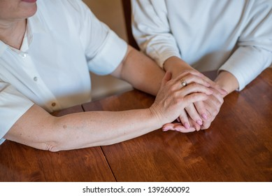 Elderly mother and her daughter holding hands while sitting at the table.Close up on women of different generations holding hands. Close Up Shot Of Mother And Daughter's Hands Holding