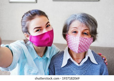 An elderly mother and a positive adult daughter have fun wearing masks on their face and take a selfie - Grandmother and a young granddaughter take a joint photo on a mobile phone camera - New Normal