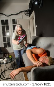 Elderly mother is trying to wake up her son who is sleeping long into the day, striking him with a house slipper to get his attention