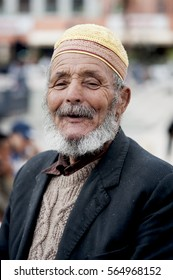 Elderly Muslim man, Ouarzazate, Morocco, 2016. An elderly bearded Muslim man smiling and enjoying the early evening gathering in the main square of Ouarzazate in the south of Morocco.
