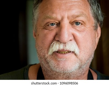 Elderly mustached man close-up portrait. Real people