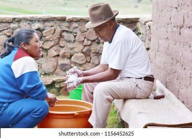 Elderly native american man washing clothes in the countryside.  His growth daughter looking at him.