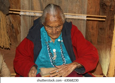 elderly Navajo woman demonstrating weaving of wool in a hogan in monument  valley