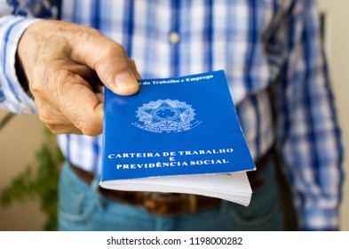 "Elderly old male hands worker holding portfolio work permit of Ministry of Labor and Social Security of Brazil(Translation: ""Work Permit, Ministry of Labor and Social Security of Brazil CTPS"").Senior."