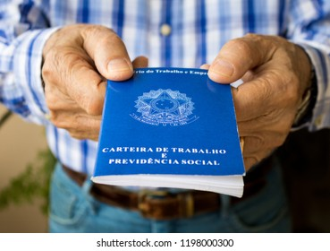 """Elderly old male hands worker holding portfolio work permit of Ministry of Labor and Social Security of Brazil(Translation: """"Work Permit, Ministry of Labor and Social Security of Brazil CTPS"""").Senior."""