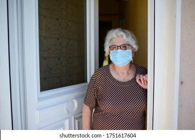 ältere ältere ältere ältere ältere ältere Frau, die die Haustür öffnet und zu Hause Menschen mit einer chirurgischen Maske empfängt, um eine Kontamination mit Kokosnuss und Koronavirus zu vermeiden