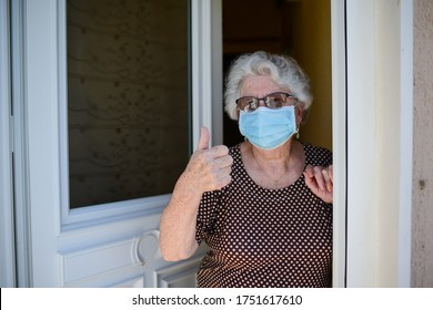 elderly old senior woman opening front door of house and welcoming people at home wearing a surgical mask to avoid covid19 and coronavirus contamination