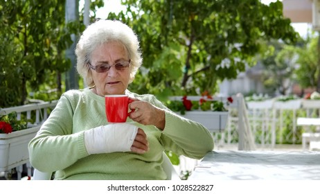 elderly old woman with brokenn hand drinking coffee tea outdoor sitting