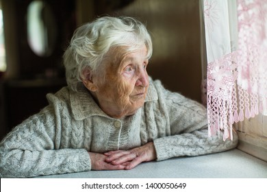An elderly old woman looks sadly out the window. Care for lonely pensioners.