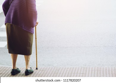 elderly old woman with walking stick stand waiting on footpath sidewalk crossing the street alone. concept senior across the street to zebra crosswalk.