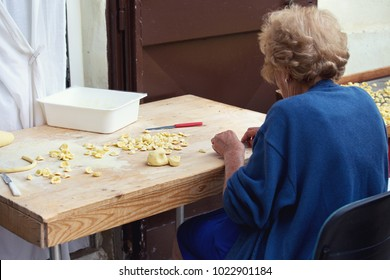 Elderly (old) woman's making homemade traditional pasta (orechiette) on wooden board in Bari, Italy. Selective focus