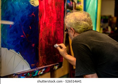 Elderly painter working in his atelier. The male model of beard and white hair is painting a new painting in his atelier filled with objects.