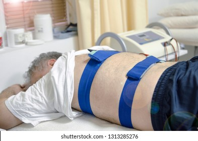 Elderly patient have electrophoresis procedure healing with electrodes on his back. Electronic Massage for osteopathy in chiropractor clinic.Back pain treatment physical therapy