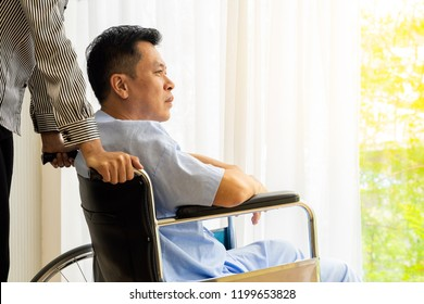 Elderly patient and his relative on wheelchair is looking through the window