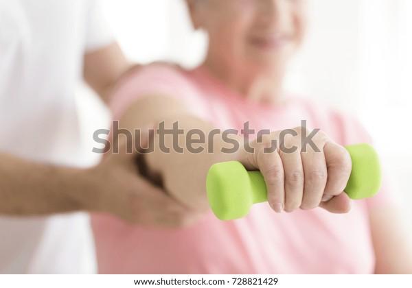 Ältere Patienten, die während der isometrischen Physiotherapie eine kleine Hantel in der rechten Hand halten