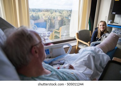 Elderly patient at hospital visited by grandchild