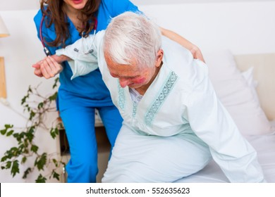 Elderly patient starting to walk, a beautiful brunette geriatric doctor helping her first steps.