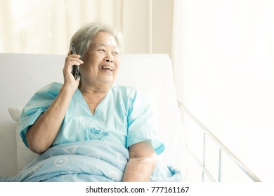 Elderly patient using mobile phone in bed. Elderly happy chinese woman in hospital bed talking to her relatives with her mobile phone. Connected world concept.