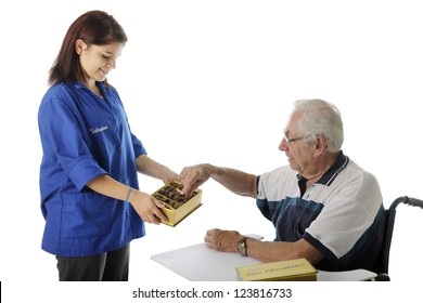 An elderly patient in a wheelchair taking a piece of chocolate from a pretty teen hospital volunteer.  On a white background with space over man's head for your text.