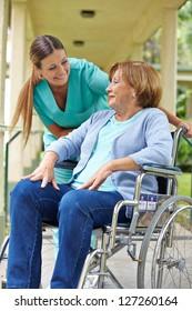 Elderly patient in wheelchair talking to nurse in a hospital garden