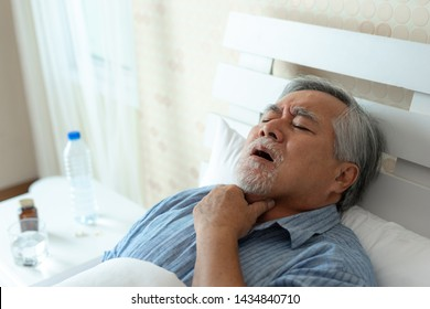 Elderly patients in bed, Asian senior man patients sore throat hands on neck - medical and healthcare concept