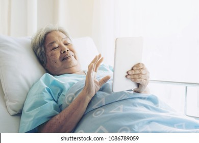 Elderly patients in hospital bed patients using smart phone call to descendant relatives feel happy ness - medical and healthcare concept