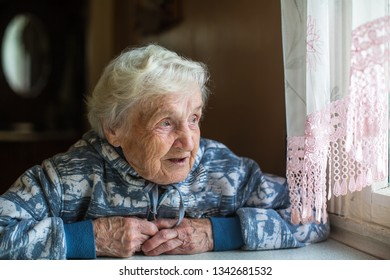 Elderly pensioner woman looks out the window. Old lady, granny.