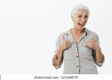 Elderly people can rock too. Portrait of charming enthusiastic granny with grey hair in loose shirt showing thumbs up in like gesture winking and gazing at camera approving awesome idea