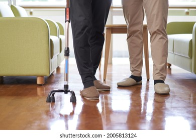 Elderly people and caregivers walking with a quadruped cane