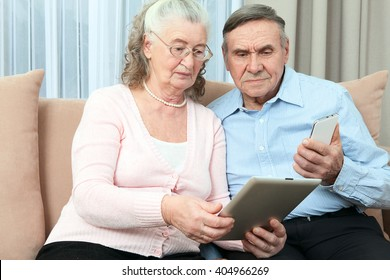 Elderly people. Elderly couple having fun in communicating with the family on the internet in the comfortable living room