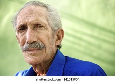 Elderly people and emotions, portrait of serious senior caucasian man looking at camera against green wall