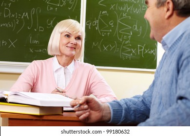 Elderly people looking at each other with a smile during the break between lessons