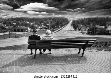Elderly people are sitting on a green bench. Looks into the distance on the road and a beautiful sky with clouds and forest.