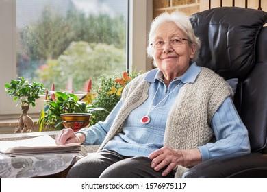 Ältere Personen mit Notknopf im Wohnzimmer sitzen