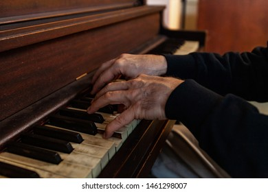 Elderly person plays music on piano. A close-up view on the arthritic hands of an old man playing a melody on an antique wooden piano. Worn keys are seen in the foreground with copy-space.