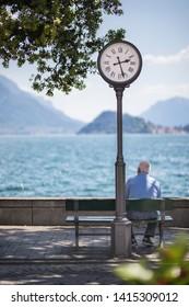 Elderly person sitting near city clock
