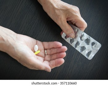 Elderly person taking medication, two different pills