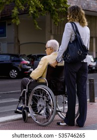Elderly person, in a wheelchair, pushed by a woman