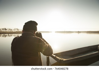 elderly photograper on lake