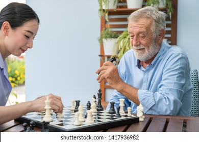 Elderly playing chess with nurse caregiver in nursing home for leisure